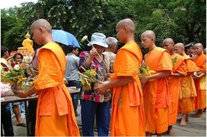 Monks receive food brought by people