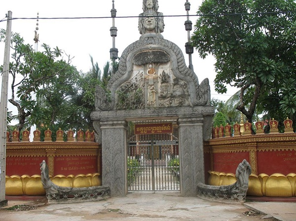 The front gate integrates bayon-style heads and a scene in relief of the Buddha seated under a tree