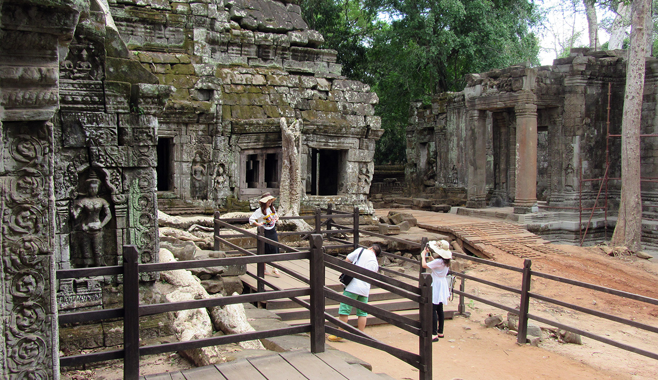 Tourists are taking photos with the embossments in Ta Prohm temple