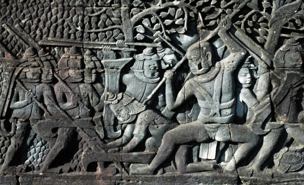 Tourists are fasinated by reliefs at Angkor Wat